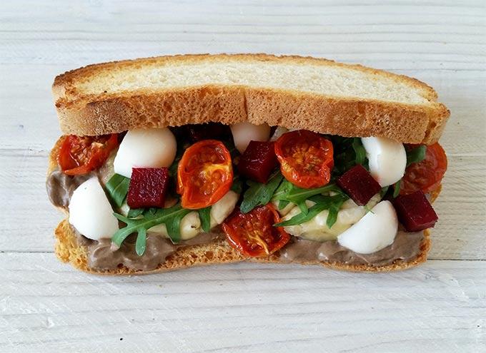 Panino con melanzane, barbabietola, pomodorini confit e maionese vegana all'aglio nero.